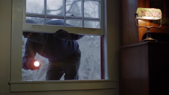 Medium shot burglar with flashlight opening window and climbing into house