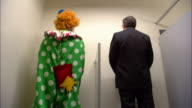 Medium shot businessman and clown using urinal / looking at each other + exchanging greetings / low angle