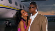 Medium shot Businessman and diva kissing and embracing on runway near private airplane / Long Beach, California, USA