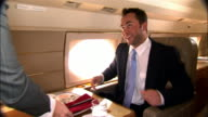 Medium shot Businessman eating sushi with chopsticks in private airplane