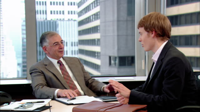Medium shot businessman interviewing young man for job/ pan businessman shaking young man's hand/ New York, New York