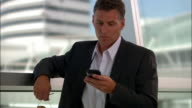 Medium shot businessman on PDA at airport/ man waving to someone/ Seattle