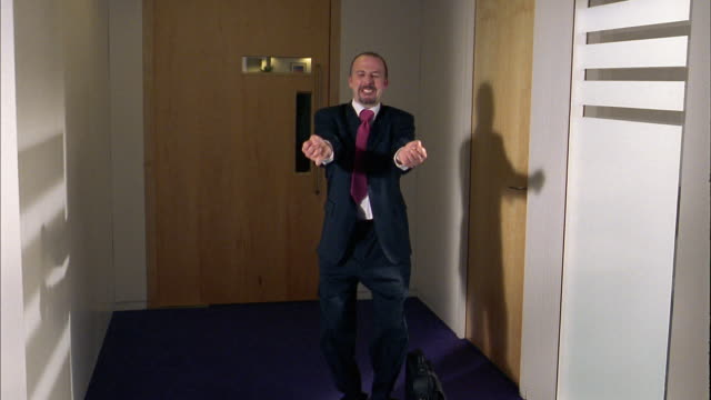 Medium shot businessman setting down briefcase and dancing in hallway