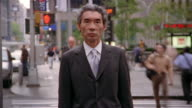 Medium shot businessman standing still with time lapse up pedestrians and traffic in background / New York City