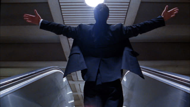 Medium shot businessman stretching arms on escalator