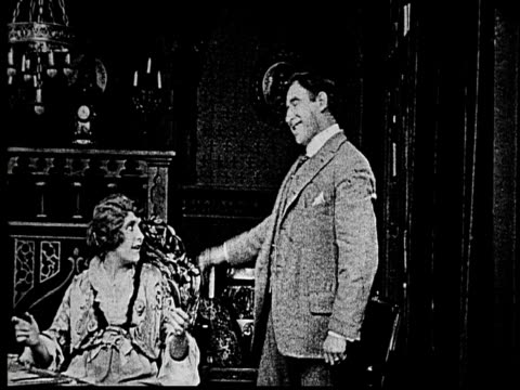 1914 B/W Medium shot Businessman talking to wealthy woman in ornate room