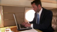 Medium shot Businessman using laptop and reading documents in private airplane