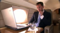 Medium shot Businessman using laptop in private airplane