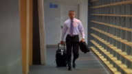 Medium shot businessman walking down hallway with suitcase/ Seattle, Washington