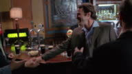 Medium shot businessmen meeting at pub after work / toasting