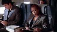 Medium shot businesswoman reading magazine on airplane / reclining seat and closing eyes