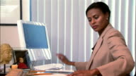 Medium shot Businesswoman using computer and reading documents at desk in office