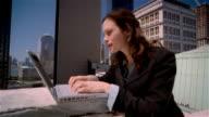 Medium shot businesswoman using laptop on roof / pummping her fist / New York City