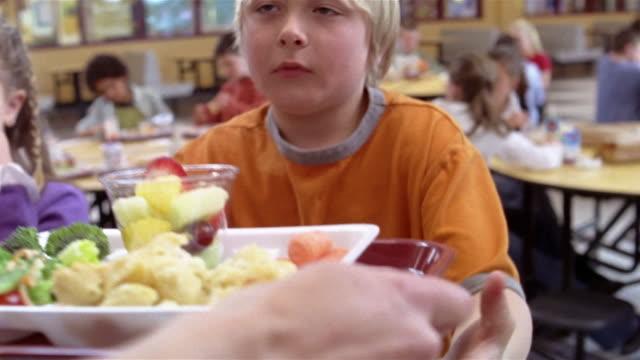 Medium shot cafeteria worker handing lunch trays to children/ Goram, Maine