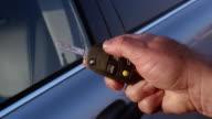 Medium shot car door / close up thumb pressing keychain remote and locking door