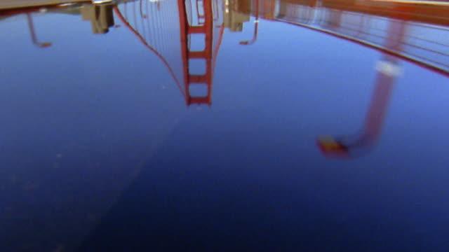 Medium shot car hood reflection driving over Golden Gate Bridge