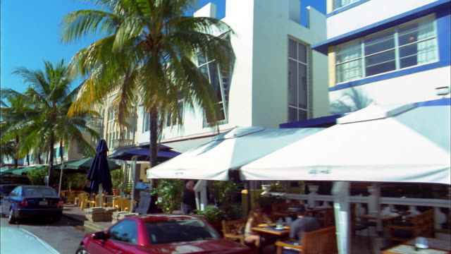 Medium shot car point of view passing restaurant awnings, cafes and palm trees / Miami Beach, Florida