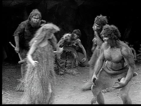 1914 B/W Medium shot Cavemen surrounding cavewoman and dragging her down by her hair