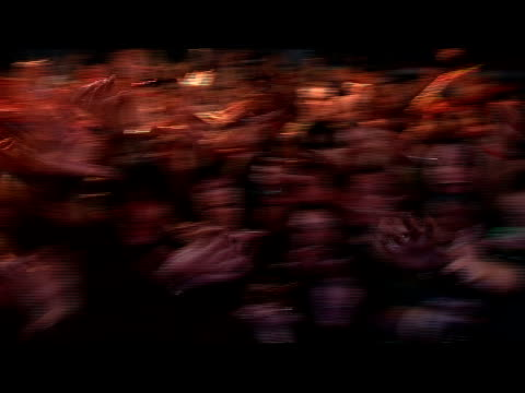 Medium shot POV of celebrity on stage as fans reach up with grabbing hands/ London, England