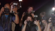 Medium shot celebrity POV of paparazzi taking photos at event/ Los Angeles