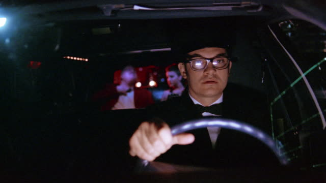 Medium shot chauffeur driving limousine with passenger in back / partition being raised