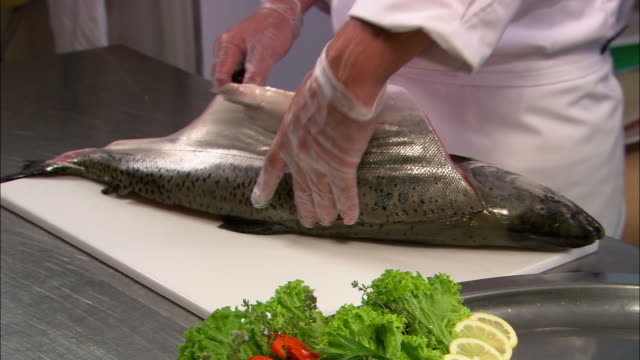 Medium shot chef filleting salmon on cutting board / lifting fillet onto plate of garnishes / Auckland