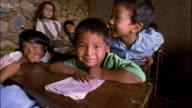Medium shot children at desks posing / Nepal