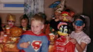 1958 medium shot children dressed up in Halloween costumes sitting around table and smiling at CAM