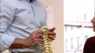 Medium shot chiropractor showing woman model of human spine / zoom in pointing out vertebrae / tilt up to his face / pan to patient's face