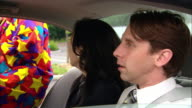 Medium shot clown getting into back seat of car with carpooling man and woman