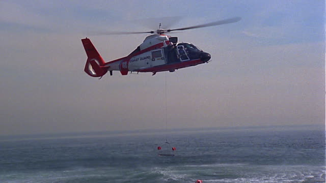 Medium shot Coast Guard helicopter lowering rescue equipment into Pacific Ocean / zoom in to rescuer