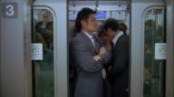 Medium shot commuters riding subway train / doors closing and train taking off / Tokyo, Japan
