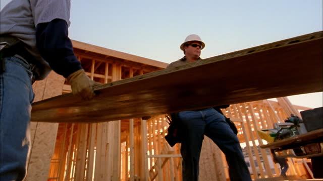 Medium shot construction workers loading wood panels into back of truck / Phoenix, Arizona