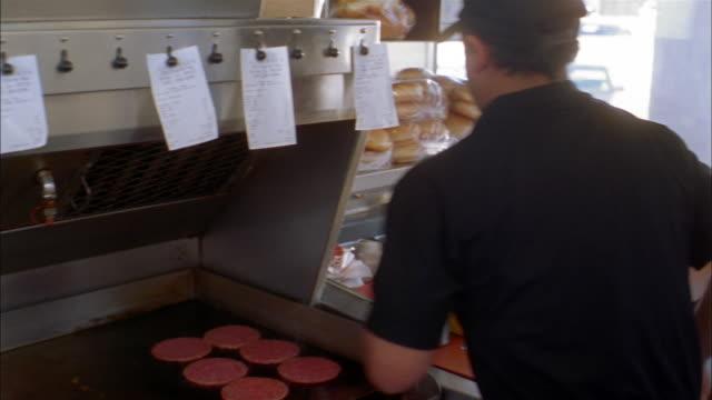 Medium shot cook putting raw hamburger patties and buns on grill