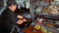 Medium shot cook removing cheeseburgers from grill in fast food restaurant kitchen