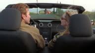 Medium shot couple driving down road in convertible/ couple kissing/ Napa Valley, California
