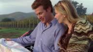 Medium shot couple looking at map at vineyard next to red convertible/ Napa Valley, California