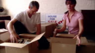 Medium shot couple packing books in to moving boxes