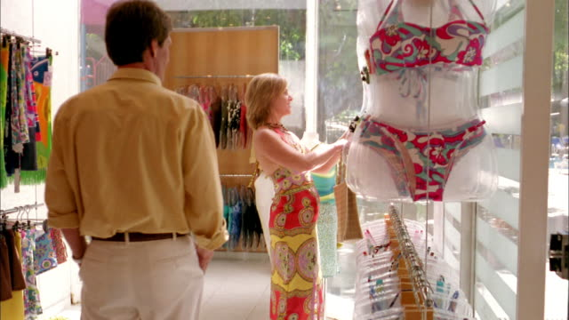Medium shot couple shopping for swimsuits in store / woman holding up bikini