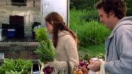 Medium shot couple smelling fresh herbs at famers' market
