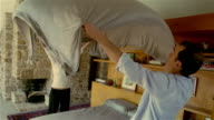 Medium shot couple stretching out sheet over their heads / making bed