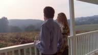 Medium shot couple walking on porch at vineyard, drinking wine and holding hands/ couple kissing/ Napa Valley, California