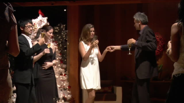 Medium shot Couples drinking champagne and celebrating at Christmas party