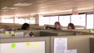 Medium shot co-workers having conversation over the tops of their cubicles / shaking hands