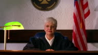 Medium shot crane shot senior female judge sitting at bench / American flag in background