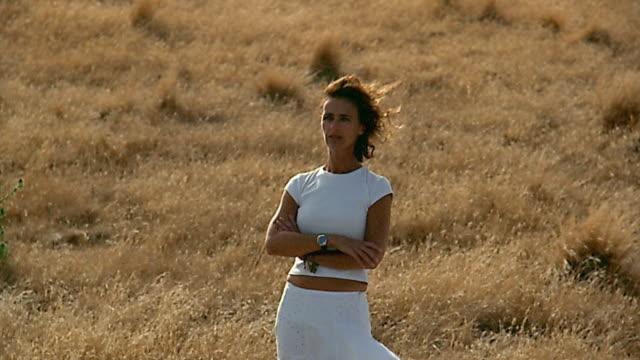 Medium shot crane shot to long shot woman standing on cliff / Flinders, Mornington Peninsula, Australia