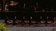 Medium shot crew team rowing racing shell on Charles River
