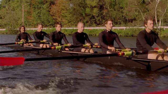 Medium shot crew team rowing racing shell on Charles River