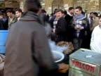Medium shot Crowd of pedestrians walking past vendor selling steaming food on street/ Turkey