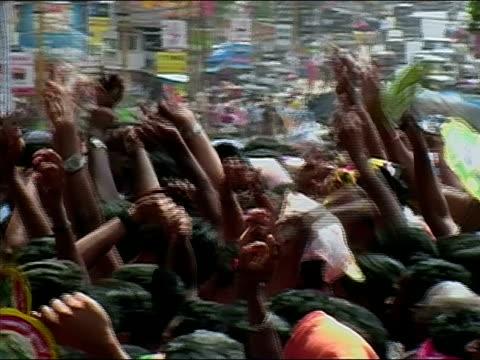 Medium shot crowd waving fans and raising arms at Thrissur Pooram elephant festival / Thrissur, Kerala, India